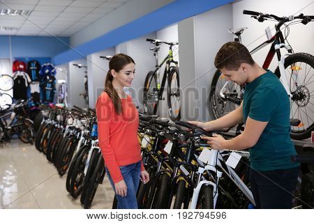 Young man showing bicycle to girl in shop