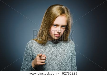 Closeup Thoughtful or contemptuous girl show at camera isolated on Gray.