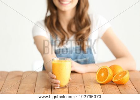 Weight loss concept. Beautiful young woman sitting at table with healthy delicious smoothie on white background