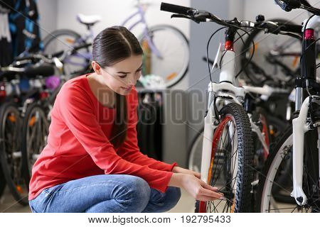 Girl checking bicycle wheel in shop