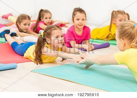 Group of happy 5-6 years old kids practicing gymnastics with female teacher, stretching laying on the mats