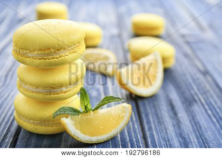 Tasty lemon macarons on wooden table, closeup