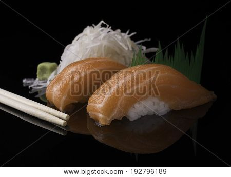Two pieces of Japanese salmon sushi on a black reflective surface served with wasabi and white radish.