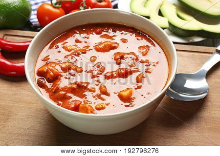 Bowl with delicious chili turkey on wooden board, closeup