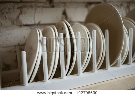 Ceramic white plates in rustic wooden dish holder on shelf with white brick wall in background