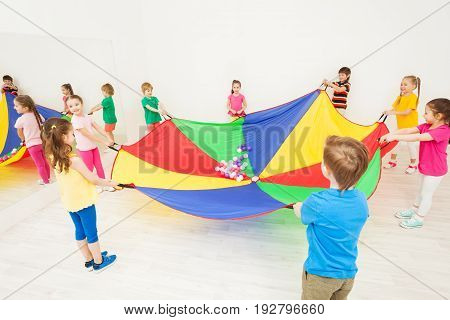 Happy children gathering around the party-coloured parachute and playing games in gym