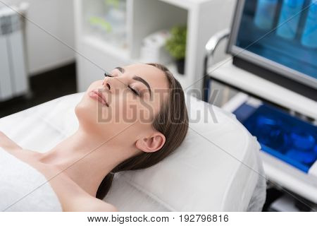 Beauty concept. Close up of charming girl with fresh and clean skin. She is lying on massage table with closed eyes. Interior with cosmetic background