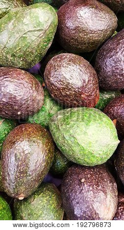 Green and brown skinned avocados in a group