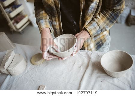 Woman's hands making clay bowl ware in pottery studio