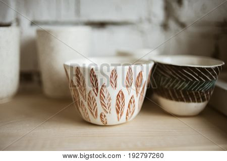 Glazed ceramic painted cups with pattern on wooden shelf in studio