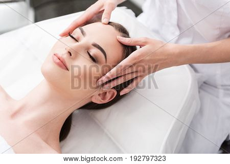 Nice time. Close up top view portrait of charming woman is lying on table with closed eyes. Professional cosmetologist is making face massage in spa salon