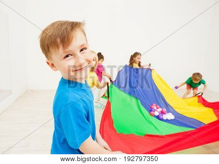 Close-up portrait of happy six years old boy waving parachute full of colorful balls, standing against background with copy-space