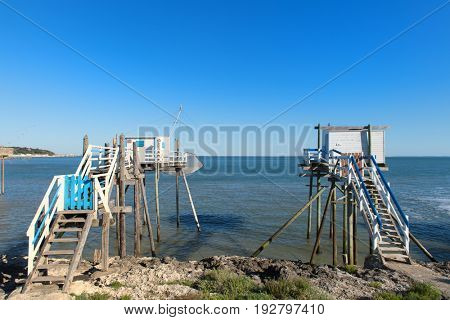 wooden fisherman huts on poles at the coast from the French Gironde