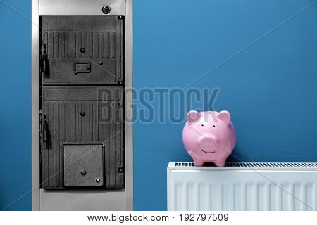 Energy savings concept. Solid fuel boiler and radiator with piggy bank on color background