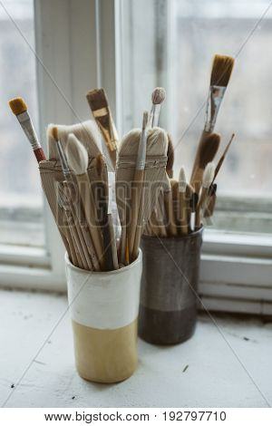 Pottery tools brushes with wooden holders in ceramic vases on windowsill in pottery studio