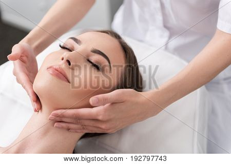 Great pleasure. Close up portrait of tempting young woman is lying on couch with closed eyes and enjoying anti-aging facial massage at spa salon. Hands of cosmetologist are stroking her neck