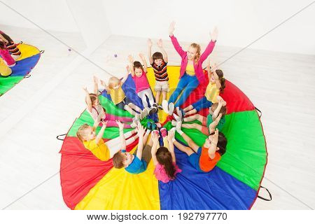 Top view portrait of happy children and female animator playing circle games, sitting on colorful parachute in sport hall