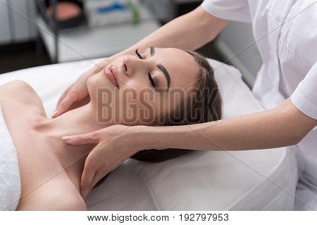 Feeling pleasure. Close up top view portrait of lovable brunette girl is getting facial massage while lying on table with closed eyes. Professional cosmetologist doing face care for young woman