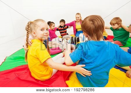 Portrait of blond preschool girl playing games with friends, hugging and sitting in circle on colorful parachute