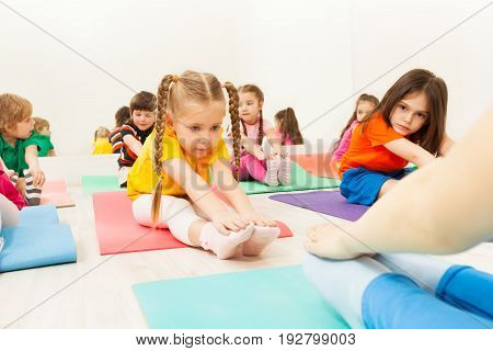 Portrait of diligent five years old girl doing stretching exercise, sitting on mat in the gym center, among her friends