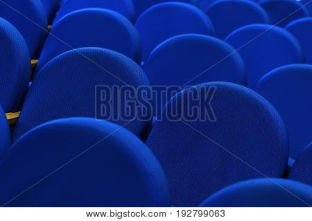 Seats in conference room for business meeting, rows of blue textile comfortable chairs in empty hall, selective focus