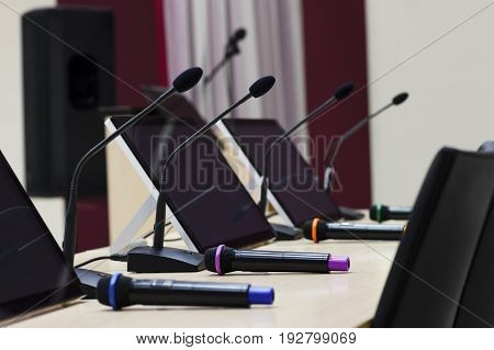 Conference room ready for business meeting, table with microphones, displays and chairs for participants in row, selective focus