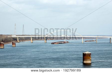 horizontal image of two barges coming down the lake under a bridge with product.