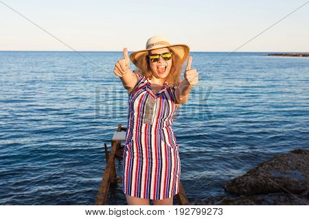 Young beautiful woman showing thumbs up on the beach.