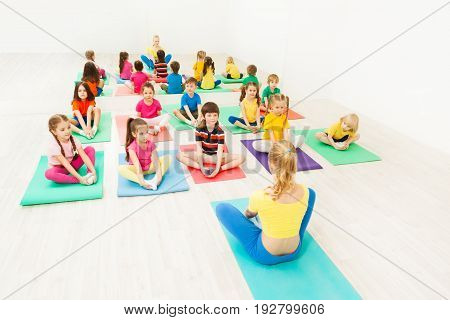 Female instructor giving yoga class for 5-6 years old kids in light exercise room