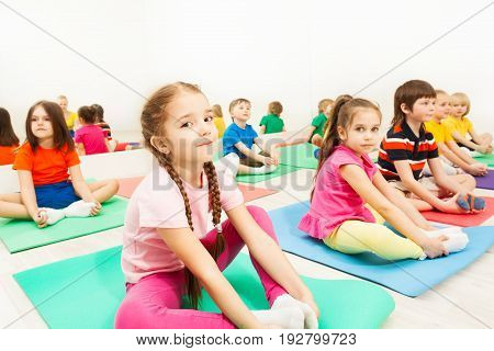 Portrait of cute six years old girl doing butterfly stretch with her friends in kid's gymnastics group