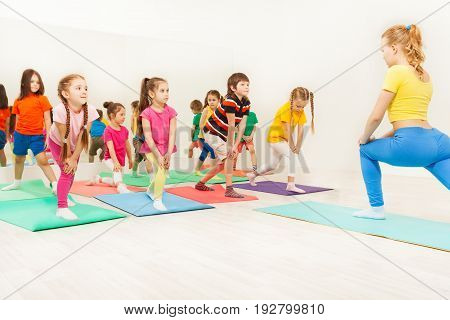 Group of happy six years old kids and female instructor doing gymnastic exercises in fitness class