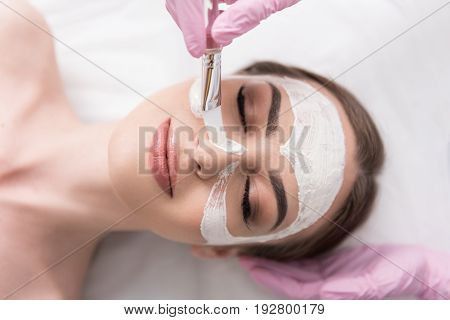 Pleasant time. Close up top view portrait of enjoyable young woman is lying on couch with pleasure while beautician is applying facial mask with brush