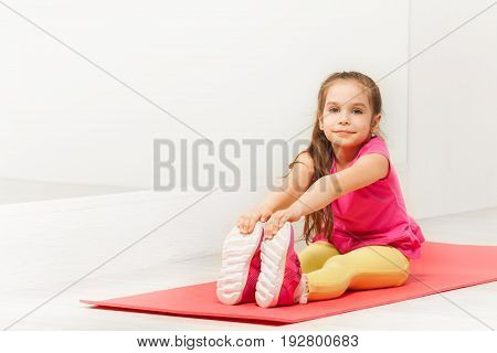 Portrait of six years old girl stretching legs, sitting on mat next to the mirror, during gymnastic lesson