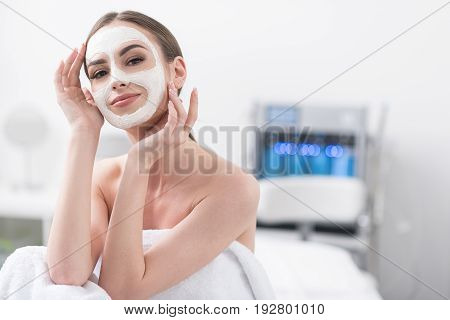 Feeling good. Portrait of pleasant charming girl is enjoying facial treatment. She is sitting on couch and looking at camera with slight smile while touching her face. Copy space in the right side