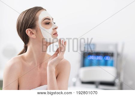 Pleasant sensations. Profile of elegant naked girl in towel, which is resting in spa center. She is looking aside thoughtfully while touching her face with mask. Copy space in the right side