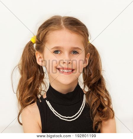 Portrait of happy seven years old girl wearing necklace, smiling at camera over white background