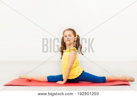 Side view portrait of seven years old girl performing front split during gymnastic lesson