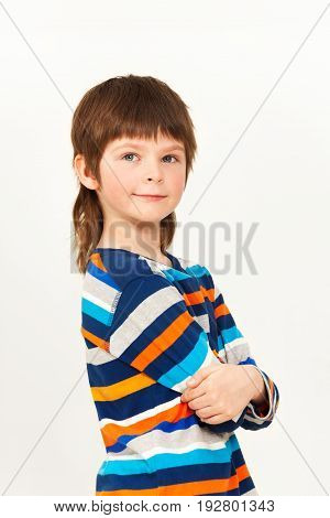 Portrait of seven years old boy standing confidently with his arms folded