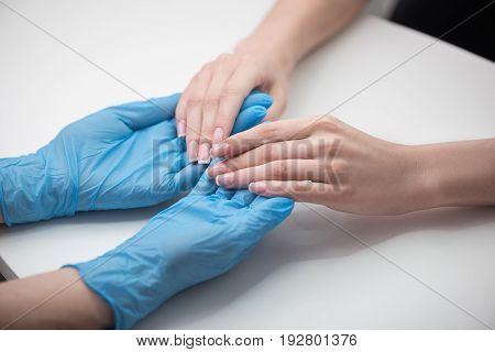 Nails caring. Young women are sitting at table. Close up top view of fingernails of client, which is holding manicurist wearing blue gloves