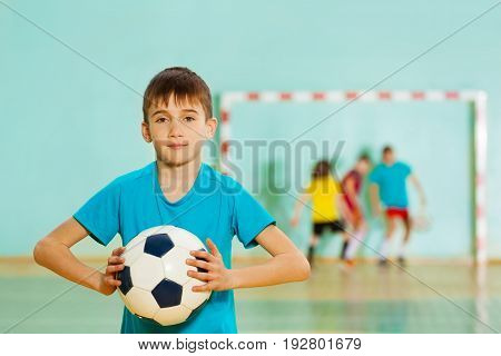 Portrait of 12 years old boy, football player, ready to throw soccer ball into the air in sports hall