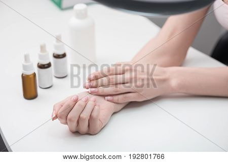 Elegant lady is sitting at desk. Close up of beautiful fingernails with french manicure of young woman. Professional care on background