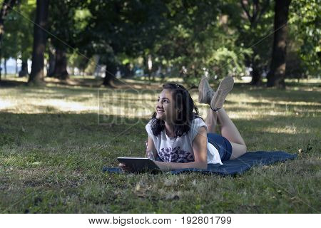 She Uses A Tablet And Relaxes In Nature