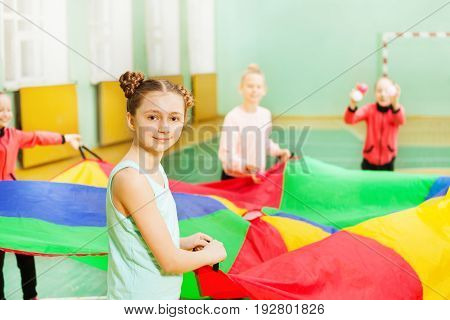 Portrait of 12 years old girl playing parachute games with her friends in sports hall
