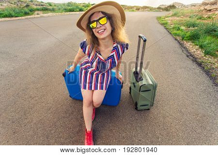 Happy traveler woman sitting on a suitcase on the road and smiling. Concept of travel, journey, trip.