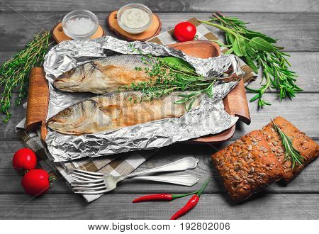Grilled Whole Trout On An Aluminum Foil On A Wooden Log