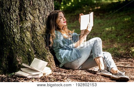 Girl reading a book near a tree in the park