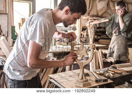 male carpenter working with a wood product, hand tools, close up