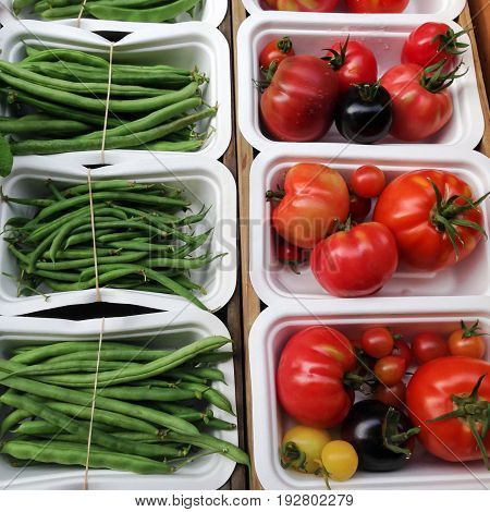 Organic tomatoes and green french beans in compostable packaging made from sugarcane fibre at a farmers market in New Zealand NZ