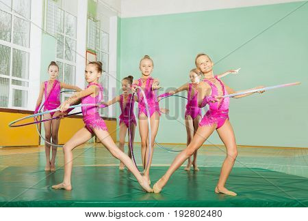 Group of preteen girls, professional gymnasts present their performance with hula hoops in sports hall