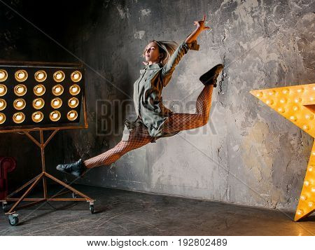 portrait of beautiful attractive blonde woman dancer jumping high in the loft